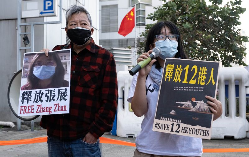 Activists Lee Cheuck-yan (L) and Chow Hang-tung (R) holding placards expressing their opinion during the demonstration..Pro-democracy activists demonstrate outside China's Liaison Office in Hong Kong to demand the release of twelve local young activists facing trial on the mainland and Chinese citizen journalist Zhang Zhan. The twelve activists have been detained on the mainland after a failed attempt to flee to Taiwan by a speedboat while Zhang has been sentenced to four years in prison over her reporting of the coronavirus outbreak in Wuhan early this year.