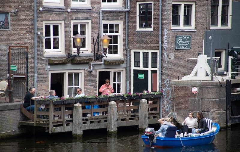 """Daily life in the canals of Amsterdam in the Netherlands with people enjoying drinks next to the water or having a boat tour. The 17th century canal ring area, known as """"Venice of the North"""" is a UNESCO World Heritage Site in the Dutch capital. The scenes with the overcrowded tourists didn't occur in April as there were travel restrictions applied due to Covid-19 Coronavirus pandemic. Amsterdam, the Netherlands on April 28, 2021. Daily Life In Amsterdam, Netherlands - 28 Apr 2021,Image: 628526544, License: Rights-managed, Restrictions: , Model Release: no, Credit line: Profimedia"""