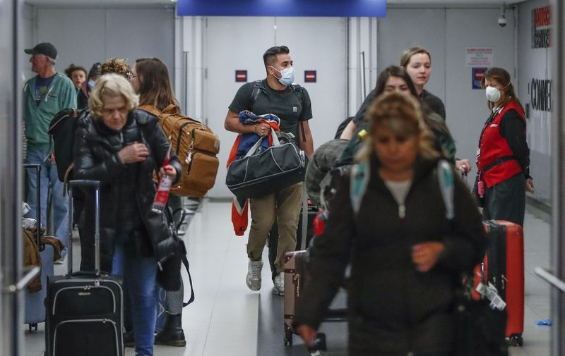 """(FILES) In this file photo taken on March 15, 2020, travelers arrive at the international terminal of the O'Hare Airport in Chicago, Illinois. - Air passengers bound for the US will require a negative Covid-19 test within three days of their departure, the Centers for Disease Control and Prevention (CDC) said on January 12, 2021. """"Testing does not eliminate all risk but when combined with a period of staying at home and everyday precautions like wearing masks and social distancing, it can make travel safer,"""" said CDC Director Robert Redfield. (Photo by KAMIL KRZACZYNSKI / AFP)"""