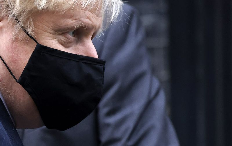 Britain's Prime Minister Boris Johnson, wearing a face covering due to the COVID-19 pandemic, leaves 10 Downing Street in central London on November 26, 2020, after coming out of self-isolation following contact with an MP who tested positive for coronavirus. - Britain's government on Wednesday unveiled plans to slash the foreign aid budget to help mend its coronavirus-battered finances, prompting one minister to quit and defying impassioned calls to protect the world's poorest people. (Photo by Tolga Akmen / AFP)