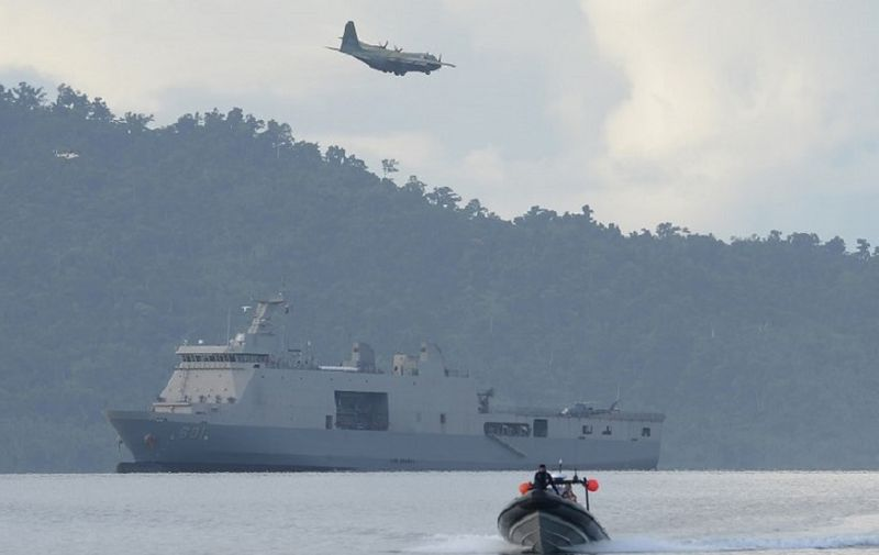 A Philippine air force C-130 cargo plane flies over Philippine navy sea lift vessel BRP Tarlac, while a speed boat loaded with US and Philippine marines sails during a simulation of a disaster drill as part of the annual joint Philippines-US military exercise at a sea port in Casiguran town, Aurora province on May 15, 2017. The Philippines and the United States launched annual military exercises on May 8, but the longtime allies scaled them down in line with President Rodrigo Duterte's pivot to China and Russia. / AFP PHOTO / TED ALJIBE