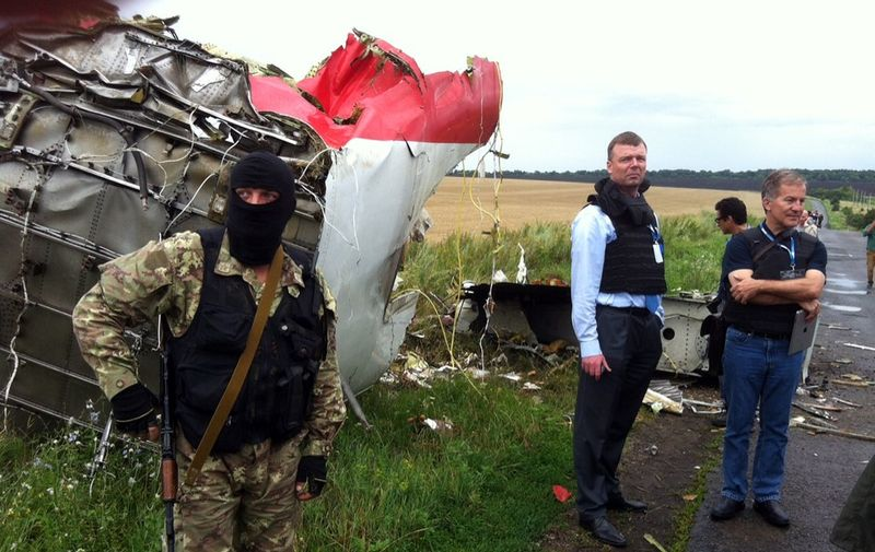 Alexander Hug (2nd L), Deputy Chief Monitor of the Organization for Cooperation and Security in Europe's  (OSCE) Special Monitoring Mission to Ukraine, visits the site of the crash of a Malaysian airliner carrying 298 people from Amsterdam to Kuala Lumpur, near the town of Shaktarsk, in rebel-held east Ukraine, on July 18, 2014. Pro-Russian separatists in the region and officials in Kiev blamed each other for the crash, after the plane was apparently hit by a surface-to-air missile. All 298 people on board Flight MH17 died when the plane crashed. AFP PHOTO / DOMINIQUE FAGET (Photo by DOMINIQUE FAGET / AFP)