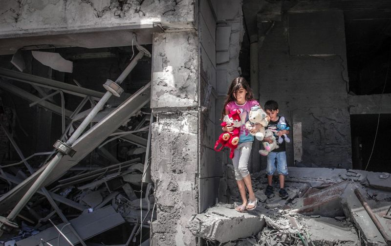 Palestinian children salvage toys from their home at the Al-Jawhara Tower in Gaza City, on May 17, 2021, which was heavily damaged in Israeli airstrikes. (Photo by ANAS BABA / AFP)