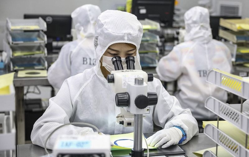 This photo taken on June 16, 2020 shows a worker producing LED chips at a factory in Huaian, in China's eastern Jiangsu province. (Photo by STR / AFP) / China OUT