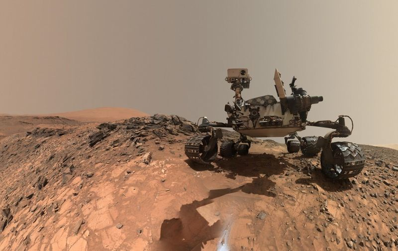 """This NASA photo released June 7, 2018 shows a low-angle self-portrait of NASA's Curiosity Mars rover vehicle at the site from which it reached down to drill into a rock target called """"Buckskin"""" on lower Mount Sharp. - NASA's Curiosity rover has found new evidence preserved in rocks on Mars that suggests the planet could have supported ancient life, as well as new evidence in the Martian atmosphere that relates to the search for current life on the Red Planet. While not necessarily evidence of life itself, these findings are a good sign for future missions exploring the planet's surface and subsurface. The new findings – """"tough"""" organic molecules in three-billion-year-old sedimentary rocks near the surface, as well as seasonal variations in the levels of methane in the atmosphere – appear in the June 8, 2018 edition of the journal Science. (Photo by Handout / NASA / AFP) / RESTRICTED TO EDITORIAL USE - MANDATORY CREDIT """"AFP PHOTO / NASA"""" - NO MARKETING NO ADVERTISING CAMPAIGNS - DISTRIBUTED AS A SERVICE TO CLIENTS"""