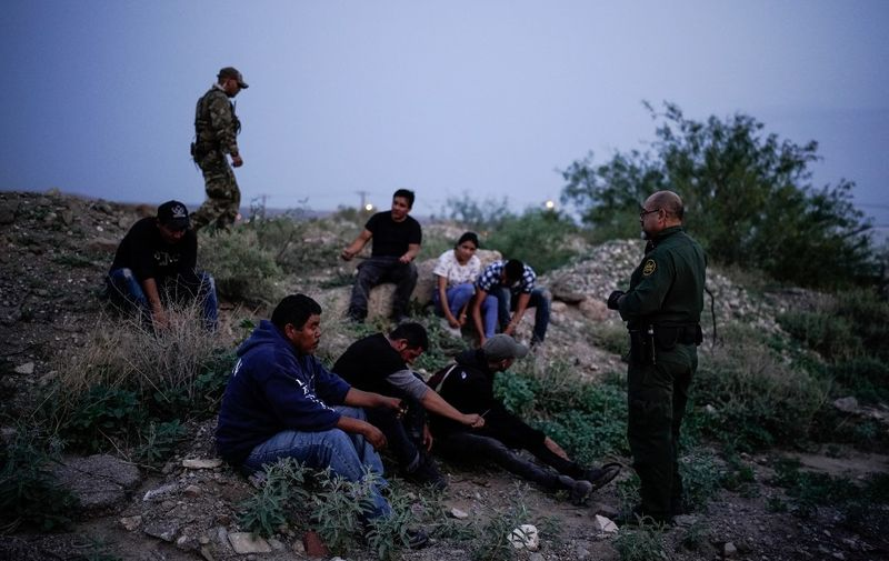 A US Border Patrol agent processes a group of migrants in Sunland Park, New Mexico on July 22, 2021. - Many advocates from national organizations urge President Biden to end Title 42 expulsions, a public health order issued in March 2020 by the Centers for Disease Control and Prevention to prevent the cross-border spread of Covid-19 resulting of hundreds of thousands of migrants expelled within hours of detention and therefore deny the opportunity to state their case for staying in the country. (Photo by PAUL RATJE / AFP)
