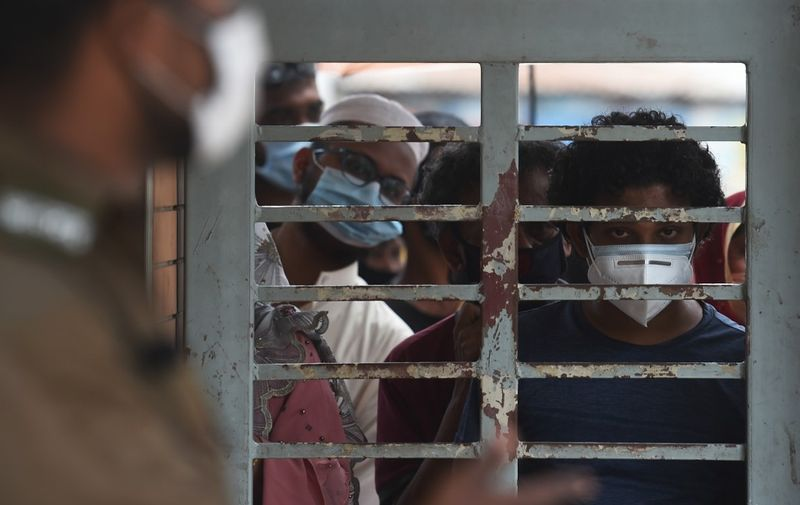 Residents waits outside the Mugda Medical College and Hospital for their turn to get tested for the COVID-19 coronavirus, in Dhaka on June 24, 2020. (Photo by MUNIR UZ ZAMAN / AFP)