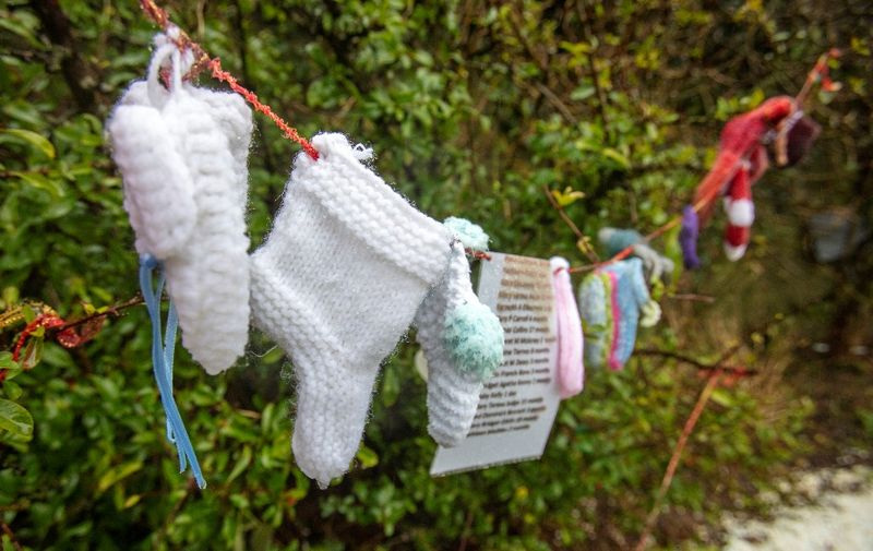 """Baby socks and hearts are pictured at a shrine in Tuam, County Galway in January 13, 2021, erected in memory of up to 800 children who were allegedly buried at the site of the former home for unmarried mothers run by nuns. - Irish prime minister Micheal Martin on Wednesday formally apologised for the treatment of unmarried women and their babies in state and church-run homes, where thousands of children died over decades. Some 9,000 children died in Ireland's """"mother and baby homes"""", where unmarried mothers were routinely separated from their infant offspring, according to an official report published Tuesday. (Photo by Paul Faith / AFP)"""