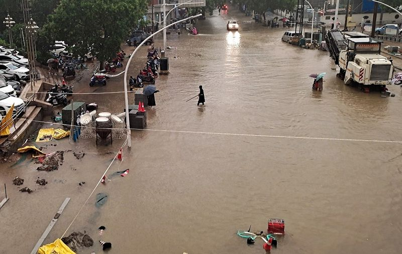 This photo taken on July 20, 2021 shows people wading through flood waters along a street following heavy rains in Zhengzhou in China's central Henan province. (Photo by STR / AFP) / China OUT