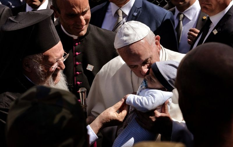 Pope Francis kisses a child at the Moria detention center in Mytilene on April 16, 2016. Pope Francis received an emotional welcome today on the Greek island of Lesbos during a visit aimed at showing solidarity with migrants fleeing war and poverty. Pope Francis, Orthodox Patriarch Bartholomew and Archbishop Jerome visit Lesbos today to turn the spotlight on Europe's controversial deal with Turkey to end an unprecedented refugee crisis. / AFP PHOTO / ARIS MESSINIS