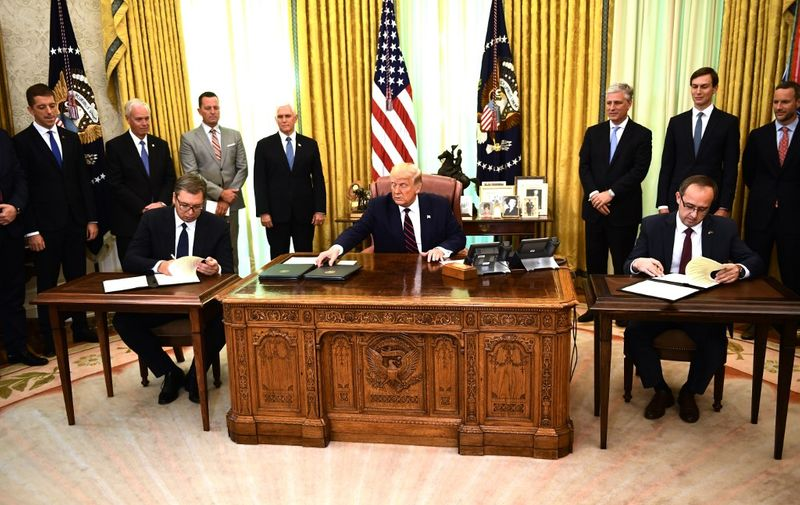 US President Donald Trump watches as Kosovar Prime Minister Avdullah Hoti (R) and Serbian President Aleksandar Vucic (L) sign an agreement on opening economic relations, in the Oval Office of the White House in Washington, DC, on September 4, 2020. (Photo by Brendan Smialowski / AFP)