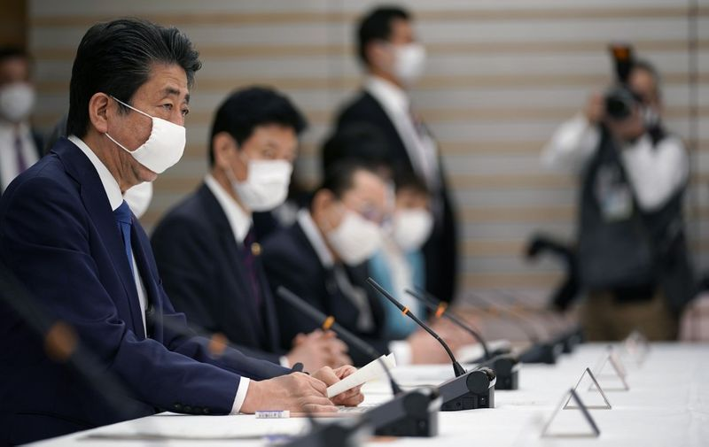 Japan's Prime Minister Shinzo Abe (L) speaks during a meeting at the headquarters for measures against the novel coronavirus disease, at the prime minister's official residence in Tokyo on April 6, 2020. - Abe said on April 6 the government plans to declare a state of emergency and proposed a stimulus package worth 1 trillion USD as new coronavirus infections spike in Tokyo and elsewhere. (Photo by Franck ROBICHON / POOL / AFP)