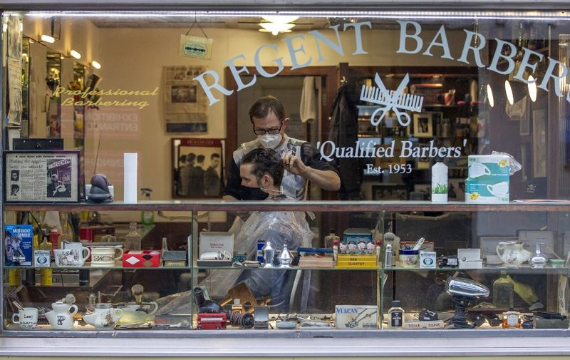 A barber wearing PPE of a face mask or covering due to COVID-19, cuts a customer's hair inside a Barbers in Dublin on October 19, 2020, amid reports that further lockdown restrictions could be imposed to help mitigate the spread of the novel coronavirus. - Ireland will crank up coronavirus restrictions, prime minister Micheal Martin said last week, announcing a raft of new curbs along the border with the British province of Northern Ireland. (Photo by PAUL FAITH / AFP)