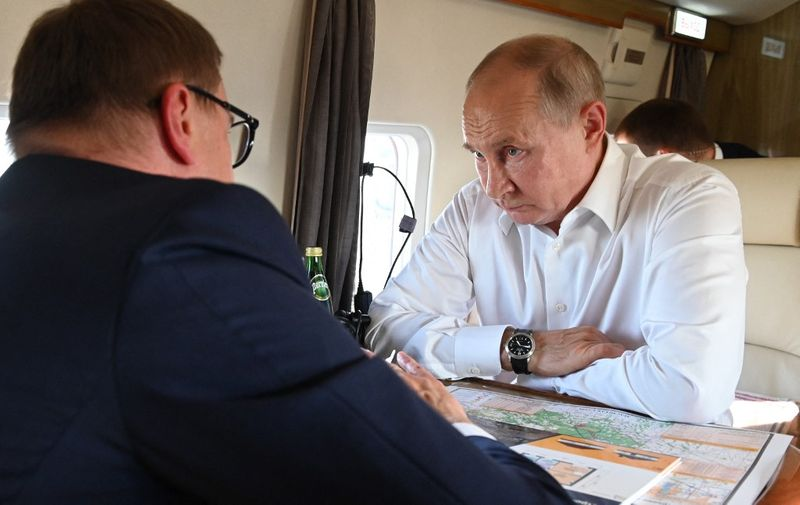 Russian President Vladimir Putin (R) speaks with Russian Ural Federal District, Chelyabinsk Region Governor Alexei Teksler (L), aboard a helicopter as they survey damage from wildfires in some areas of the Chelyabinsk Region, Russia, on August 6, 2021. (Photo by Alexey NIKOLSKY / SPUTNIK / AFP)