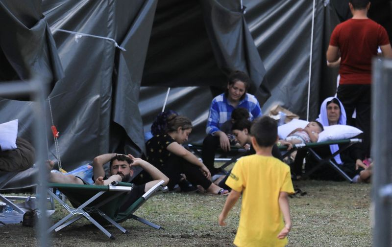 Migrants are seen through a fence as they sit and lie by tents in a camp near the border town of Kapciamiestis, Lithuania, on July 18, 2021. - Lithuania has seen more than 2,000 arrivals since the start of the year across the border from Belarus. Most of the migrants are from Iraq and Lithuanian officials suspect the influx is being orchestrated by the Russia-backed Belarusian regime as retaliation against EU sanctions. (Photo by PETRAS MALUKAS / AFP)