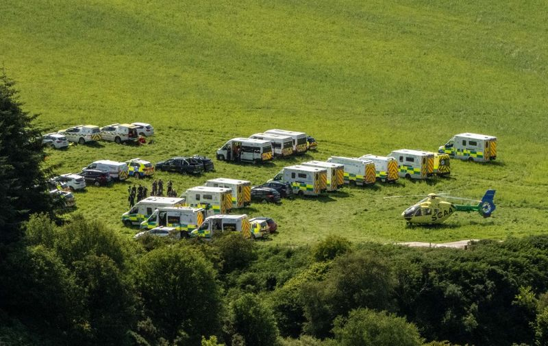 """Emergency response vehicles are parked near the scene of a train crash by Stonehaven in northeast Scotland on August 12, 2020. - A passenger train derailed in northeast Scotland on Wednesday, with reports of """"serious injuries"""" in what First Minister Nicola Sturgeon described as """"an extremely serious incident"""". (Photo by Michal Wachucik / AFP)"""