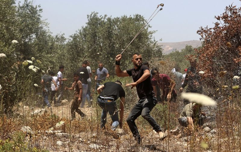 Palestinian protesters use slingshots to hurl stones at Israeli security forces amid clashes in the village of Baita, south of Nablus, in the occupied West Bank on May 28, 2021, following a demonstration against the establishment of Israeli outposts in their lands (Photo by JAAFAR ASHTIYEH / AFP)