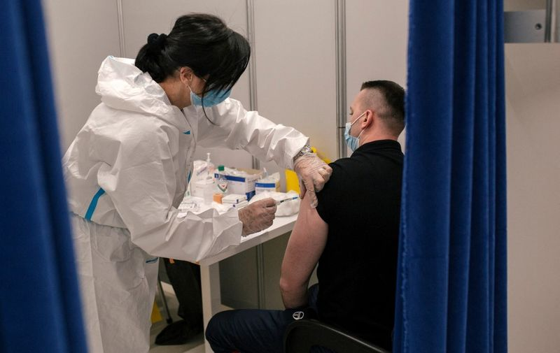 A Serbian medical worker administers a dose of a coronavirus (Covid-19) vaccine at a vaccination centre in a shopping mall of Belgrade on May 6, 2021. - Serbia's president said on May 5, 2021, that his country would pay each citizen who gets a Covid jab before the end of May, in what could be the world's first cash-for-jabs scheme. The Balkans country bought millions of doses -- from Western firms as well as China and Russia -- and briefly became a regional vaccine hub when it offered foreigners the chance to be inoculated. (Photo by Vladimir Zivojinovic / STR / AFP)