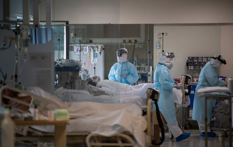 Healthcare workers attend to COVID-19 coronavirus patients at the Intensive Unit Care of the CEMTRO private clinic in Madrid on April 17, 2020. - Spain's death toll increased to nearly 19,500, government figures showed. The country reported 585 new fatalities in the past 24 hours, but said it had revised its counting mechanism, making the figures difficult to compare with previous tolls. (Photo by PIERRE-PHILIPPE MARCOU / AFP)