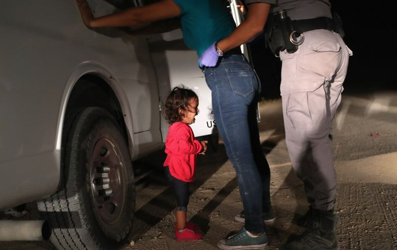 (FILES) In this file photo taken on June 12, 2018 a two-year-old Honduran asylum seeker cries as her mother is searched and detained near the US-Mexico border in McAllen, Texas. - Getty Images photographer John Moore has won the 2019 World Press Photo of the Year award with this photo of the two-year-old Honduran asylum seeker crying as her mother is searched and detained near the US-Mexico border in McAllen. (Photo by JOHN MOORE / GETTY IMAGES NORTH AMERICA / AFP)