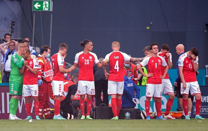 Denmark's players gather as paramedics attend to midfielder Christian Eriksen (not seen) during the UEFA EURO 2020 Group B football match between Denmark and Finland at the Parken Stadium in Copenhagen on June 12, 2021. (Photo by HANNAH MCKAY / POOL / AFP)