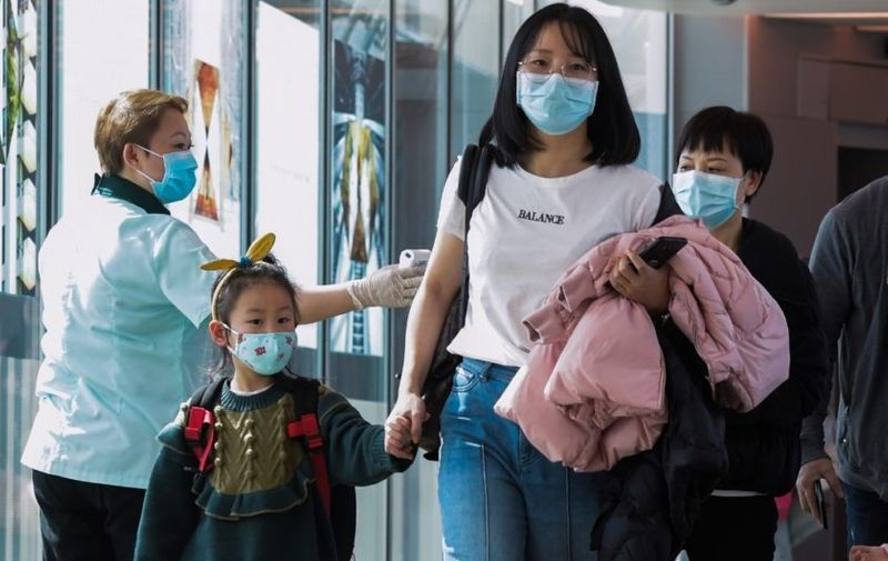 A health officer (L) screens arriving passengers from China at Changi International airport in Singapore on January 22, 2020 as authorities increased measure against coronavirus. (Photo by ROSLAN RAHMAN / AFP)