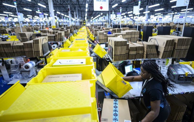 A woman works at a packing station at the 855,000-square-foot Amazon fulfillment center in Staten Island, one of the five boroughs of New York City, on February 5, 2019. - Inside a huge warehouse on Staten Island thousands of robots are busy distributing thousands of items sold by the giant of online sales, Amazon. (Photo by Johannes EISELE / AFP)