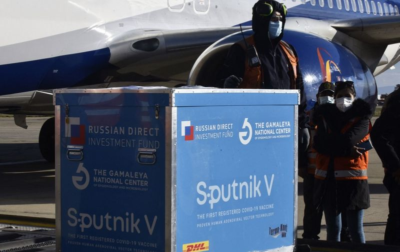 Airport workers handle a box with a batch of Sputnik V vaccines at the El Alto International Airport in La Paz, on January 28, 2021. - Bolivia received its first batch of 20,000 Russian Sputnik V vaccines to immunize the health personnel who are on the front lines of the fight against COVID-19. (Photo by AIZAR RALDES / AFP)