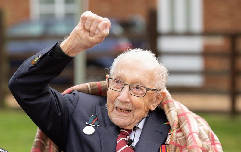 """A handout picture released on April 30, 2020 shows Captain Tom Moore waving at a flypast by Battle of Britain Memorial planes to celebrate his 100th birthday in Marston Moretaine. (Photo by Emma SOHL / CAPTURE THE LIGHT / AFP) / RESTRICTED TO EDITORIAL USE - MANDATORY CREDIT """"AFP PHOTO / CAPTURE THE LIGHT / EMMA SOHL"""" - NO MARKETING NO ADVERTISING CAMPAIGNS - DISTRIBUTED AS A SERVICE TO CLIENTS --- NO ARCHIVE ---"""