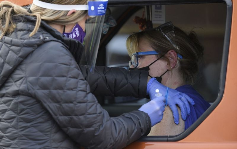 A registered nurse (L) administers the first dose of the Pfizer-BioNTech Covid-19 vaccine to a front-line health care worker under an emergency use authorization at a drive up vaccination site from Renown Health in Reno, Nevada on December 17, 2020. (Photo by Patrick T. Fallon / AFP)