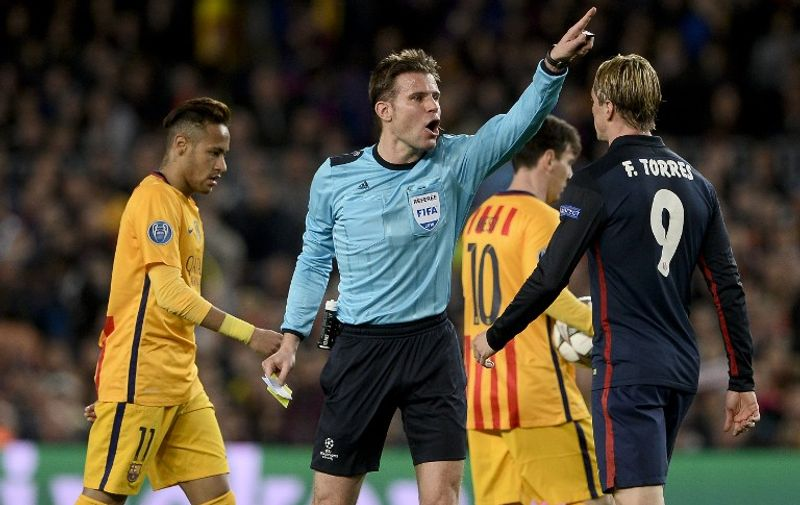 German referee Felix Brych (C) gestures after showing a yellow card to Atletico Madrid's forward Fernando Torres (R) during the UEFA Champions League quarter finals first leg football match FC Barcelona vs Atletico de Madrid at the Camp Nou stadium in Barcelona on April 5, 2016. / AFP / JOSEP LAGO