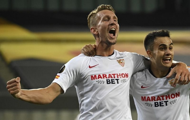 Sevilla's Dutch forward Luuk De Jong (L) celebrates scoring with his team-mate Sevilla's Spanish defender Sergio Reguilon during the UEFA Europa League semi-final football match Sevilla v Manchester United on August 16, 2020 in Cologne, western Germany. (Photo by Ina Fassbender / POOL / AFP)