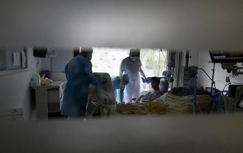 Medical staff tend to a patient infected with COVID-19 in the COVID reanimation unit at the Purpan hospital in Toulouse on February 4, 2021. (Photo by GEORGES GOBET / AFP)