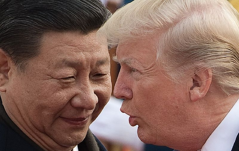China's President Xi Jinping (L) and US President Donald Trump attend a welcome ceremony at the Great Hall of the People in Beijing on November 9, 2017. (Photo by NICOLAS ASFOURI / AFP)