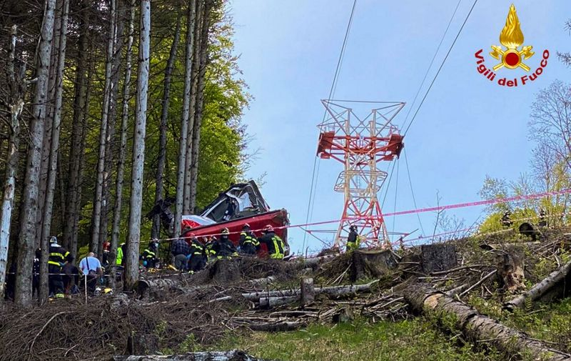 """A photo taken and handout on May 23, 2021 by The Italian Firefighters """"Vigili del Fuoco"""" shows rescuers working by a cable car that crashed to the ground in the resort town of Stresa on the shores of Lake Maggiore in the Piedmont region. - 13 people died and two children were seriously injured Sunday after a cable car crashed to the ground in northern Italy, emergency services said. (Photo by Handout / Vigili del Fuoco / AFP) / RESTRICTED TO EDITORIAL USE - MANDATORY CREDIT """"AFP PHOTO / VIGILI DEL FUOCO / HANDOUT """" - NO MARKETING - NO ADVERTISING CAMPAIGNS - DISTRIBUTED AS A SERVICE TO CLIENTS"""