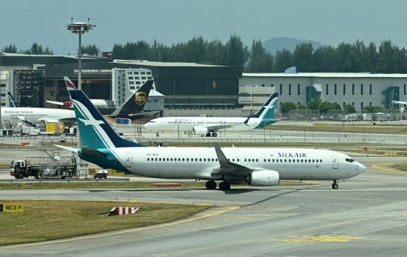 A SilkAir Boeing 737 MAX aircraft (background C) is parked on the tarmac of Changi International Airport in Singapore on March 12, 2019 while a SilkAir Boeing 737-8SA (front) taxi on a runway. - Singapore's aviation regulator on March 12, banned the use of Boeing 737 MAX aircraft in the country's airspace following a deadly Ethiopia plane crash at the weekend. (Photo by Roslan RAHMAN / AFP)