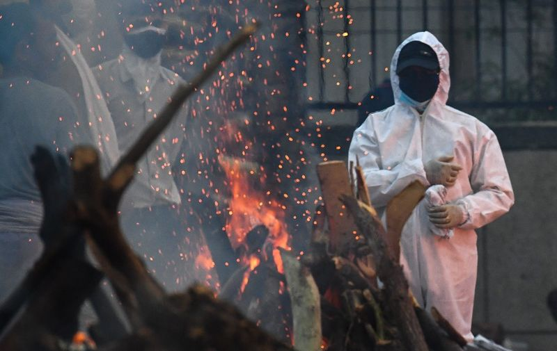A man wearing a personal protective equipment (PPE) suit stand next to the funeral pyre of his relative who died due to the Covid-19 coronavirus, at a cremation ground in New Delhi on May 6, 2021. (Photo by Prakash SINGH / AFP)