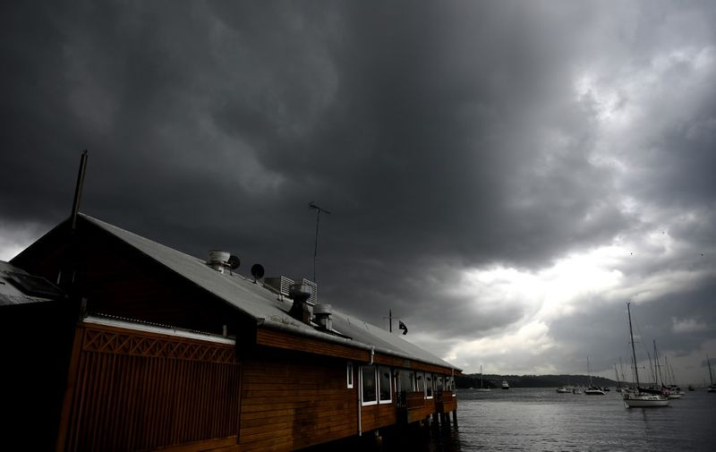 """Storm clouds gather over Double Bay in Sydney on January 20, 2020. - Thunderstorms and giant hail battered parts of Australia's east coast after """"apocalyptic"""" dust storms swept across drought-stricken areas, as extreme weather patterns collided in the bushfire-fatigued country. (Photo by PETER PARKS / AFP)"""