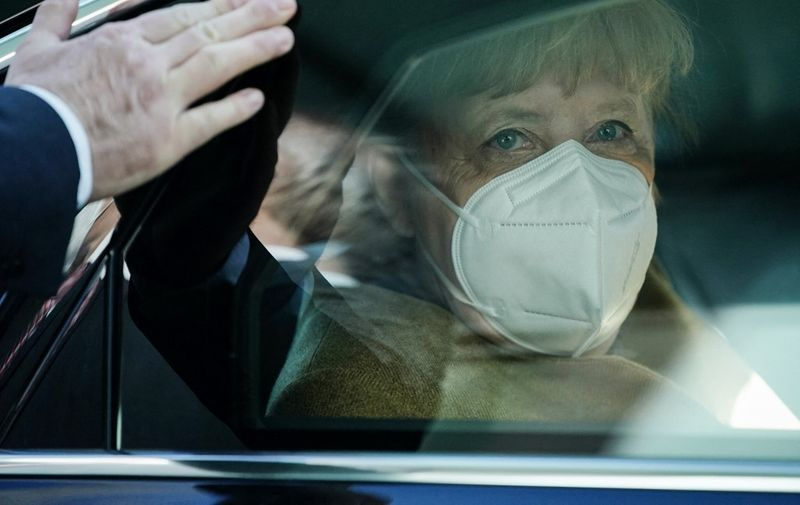 German Chancellor Angela Merkel wears a face mask as she sits in her car after holding a press conference on the Covid-19 situation in Germany at the house of the Federal Press Conference (Bundespressekonferenz), on January 21, 2021 in Berlin. (Photo by Michael Kappeler / POOL / AFP)