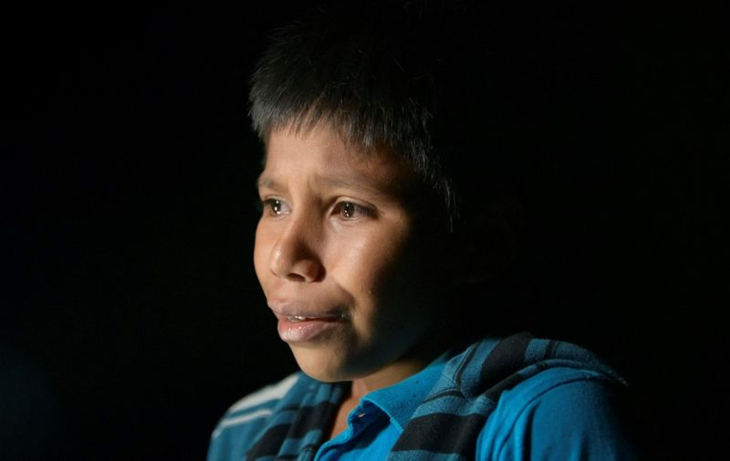 In a photo taken on March 27, 2021 unaccompanied Guatemalan child immigrant Oscar (12), who arrived illegally across the Rio Grande river from Mexico, stands after disembarking from a boat near the US border city of Roma. (Photo by Ed JONES / AFP)