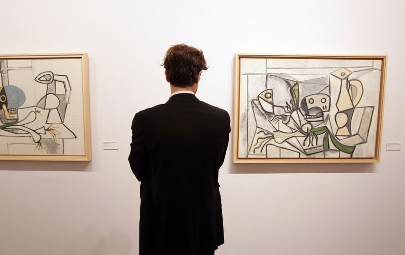 """A visitor looks at """"Nature morte a la tete de mort cruche, poireaux"""" (L) and """"Nature morte aux poireaux tete de poisson, crane et pichet"""" by painter Pablo Picasso on display at the Palazzo Grassi in Venice 09 November 2006 as part of the """"Picasso, la joie de vivre, 1945-1948"""" exhibition. The exhibition is dedicated to a four year period in Picasso's life, in the immediate postwar. Some 200 of Picasso's works are on display, including paintings, drawings, marble incisions, sculptures, and pottery. Numerous works belonging to private and public collections and 120 masterpieces from The Picasso Museum collection in Antibes. The exhibition. will be open to the pubblic  from 11 November 2006 to 11 March 2007.    AFP PHOTO / ALBERTO PIZZOLI (Photo by ALBERTO PIZZOLI / AFP)"""