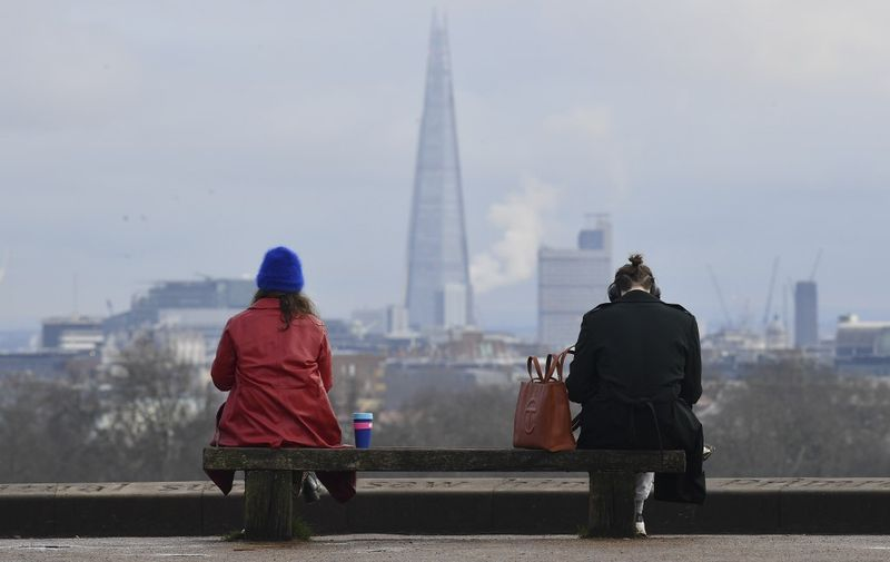 People sit at a social distance from one another on a bench on the top of Primrose Hill in London on January 12, 2021 with the Shard Tower in the background as life continues under Britain's third lockdown since the start of the coronavirus pandemic. - People who flout coronavirus lockdown rules are putting lives at risk, the British government said on Tuesday, as cases surge to record highs and rumours swirl of potentially tougher restrictions. (Photo by JUSTIN TALLIS / AFP)