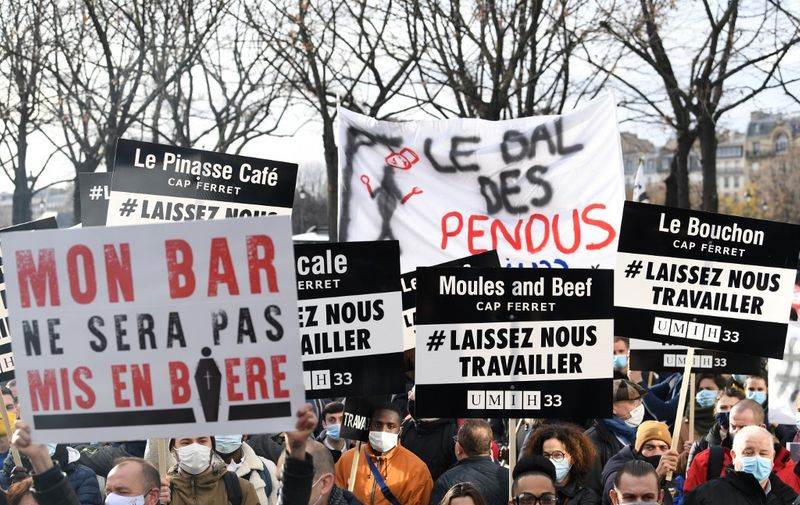 "Protesters hold placards on December 14, 2020 in Paris during a demonstration of hotel and restaurant owners  as well as tourism professionals to demand their businesses to reopen amidst the Covid-19 pandemic, caused by the novel coronavirus. The placard (L) reads ""my bar will not be placed in a coffin"". (Photo by Alain JOCARD / AFP)"