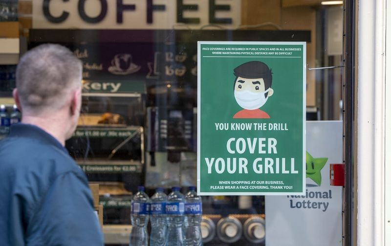 An information poster advising the wearing of face coverings as a precaution against the spread of the novel coronavirus covid-19 is seen on the window of a coffee shop in Dublin on October 21, 2020 as Ireland prepares to enter a second national lockdown to stem the spread of the virus that causes Covid-19. - Millions of people in Ireland were getting set for a second national lockdown on October 21, the first European country to take the drastic step as the continent battles a persistent surge in coronavirus cases. (Photo by Paul Faith / AFP)