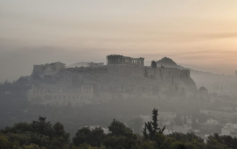 """This photograph taken on August 4, 2021 shows smoke covering Athens centre with the Acropolis in the background, due to fires burning at the foot of Mount Parnes, 30 kilometres north of Athens. - Greek firefighters said in a statement that they hope to bring a forest fire blazing near Athens under control """"in the coming hours"""". More than 500 firefighters, a dozen water-bombing planes and five helicopters have been battling the blazes outside the capital since August 3 afternoon. (Photo by LOUISA GOULIAMAKI / AFP)"""