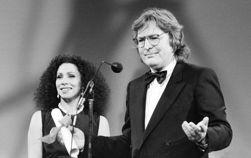 "American filmmaker Alan Parker reacts as American Opera singer Julia Migenes-Johnson looks on, after Parker was awarded with the Grand Prix Special du Jury for his film ""Birdy"" at the 38th Cannes film Festival, on May 20, 1985. AFP PHOTO/RALPH GATTI (Photo by RALPH GATTI / AFP)"