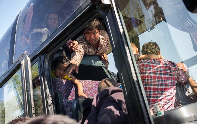 A man tries to help members of his family onto a waiting bus that will take them to Opatovac transit camp not far from the Croatian village of Bapska, on September 23, 2015. About a thousand migrants crossed the border between Serbia and Croatia this morning, and were later transported to a transit camp in Opatovac, about 20 kilometers away. AFP PHOTO/FEDERICO SCOPPA