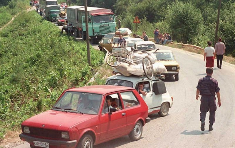 A convoy of Croatian Serb refugees from Knin wait to cross the Bosnian-Rump-Yugoslav border near the eastern Bosnian town of Raca, approximately 130 km (80 miles) west of Belgrade, 06 August. International relief agencies are bracing for a massive exodus of Serb refugees fleeing the Croatian offensive in breakaway Krajina and are beginning to organize food airlifts in order to avoid a humanitarian disaster.   AFP PHOTO (Photo by DRAGAN MILOVANOVIC / AFP)