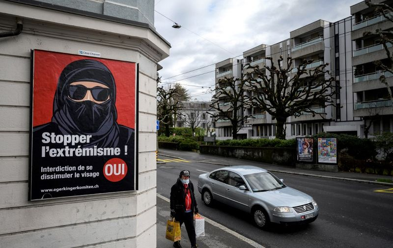 """A man wearing a face mask walks on February 4, 2021 in Lausanne past an electoral poster in favor of a """"burqa ban"""" initiative reading in French: """"Stop extremism!"""" ahead of a nationwide vote by Swiss citizen on whether they want to ban face coverings in public spaces or not. - The vote will take place on on March 7, 2021, as part of the country's famous direct democratic system. A clear majority of Swiss voters favour introducing a nationwide prohibition against wearing face-covering garments in public spaces, known as a """"burqa ban"""", a poll showed last month. (Photo by Fabrice COFFRINI / AFP)"""