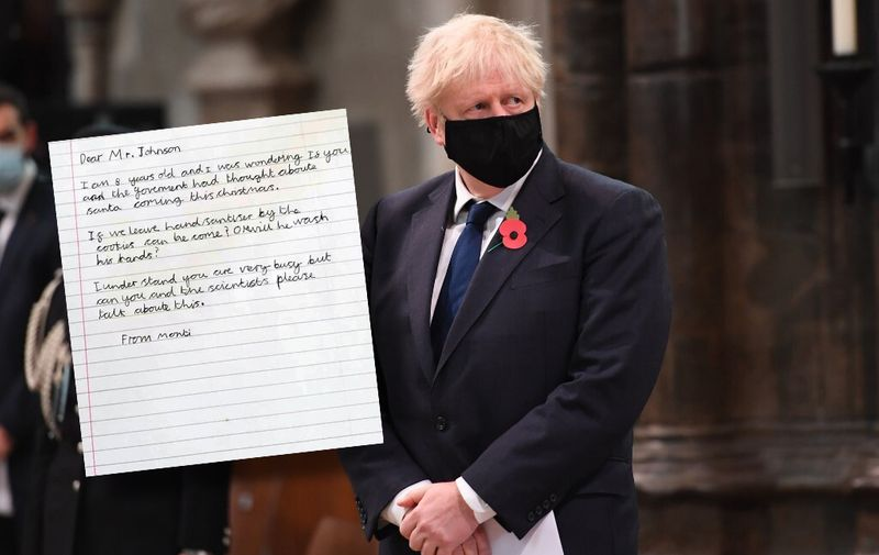 Britain's Prime Minister Boris Johnson wearing a face mask participates in a service to commemorate the centenary of the burial of the Unknown warrior at Westminster Abbey on Armistice day in London on November 11, 2020. (Photo by Jeremy Selwyn / POOL / AFP)